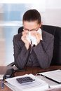 Sick young businesswoman blowing her nose in office Stock Photography