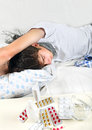 Sick young man sleeping on the bed with pills on foreground Royalty Free Stock Photo