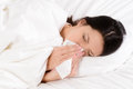 Sick young woman blowing her nose on a tissue lying in clean white bed conceptual of healthcare and seasonal flu and chills Stock Image