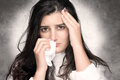 Sick young woman with flu or allergy portrait of beautiful brunette headache and blows her nose into a tissue Stock Image
