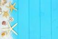 Side border of sand, seashells and starfish on blue wood Royalty Free Stock Photo