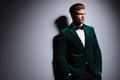 Side of a man in green velvet elegant suit relaxed young fashion model with neck bow tie looking away from the camera white Royalty Free Stock Image