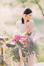 The side photo of the blurred bride holding her dark hair in the white wedding dress near the blurred bicycle with the Royalty Free Stock Photo