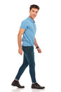 Side portrait of young man in blue shirt walking Royalty Free Stock Photo