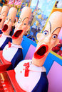 Side show carnival clowns with mouths open ready for play crazy game prizes on display in background Royalty Free Stock Photos