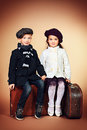 Side by side cute little boy and girl are sitting on their old suitcases retro style Stock Photos
