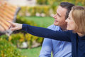 Side view of affectionate couple sitting on bench and looking ahead mature women pointing with her finger while Royalty Free Stock Photography