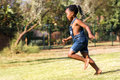 Side view of african kid running in park. Royalty Free Stock Photo
