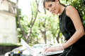 Side view of an attractive businesswoman using a laptop computer while sitting in a leafy city street during a sunny day smiling Stock Photos