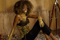 Side view of beautiful young African woman in gold accessories and touching her knees while sitting on the floor against bronze ba Royalty Free Stock Photo