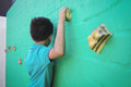 Side view of boy climbing wall Royalty Free Stock Photo