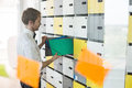 Side view of businessman putting files in locker at creative office Royalty Free Stock Photo