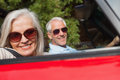 Side view of cheerful mature couple driving red cabriolet on sunny day Royalty Free Stock Photography