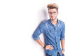 Side view of a cool man with glasses standing han on hip on white studio background Stock Photography
