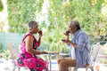 Side view of couple drinking coffee in yard Royalty Free Stock Photo