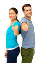 Side view of couple showing thumbs up sign portrait happy while standing back to back over white background vertical shot Royalty Free Stock Images