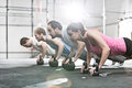 Side view of determined people doing pushups with kettlebells at crossfit gym