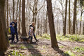 Side view of family walking with pet dog in a wood Royalty Free Stock Photo