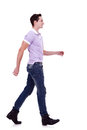 Side view of a fashion man walking forward Royalty Free Stock Photography