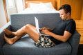 Typing new blog post. Side view of handsome young man using his laptop with smile while sitting on the couch at home Royalty Free Stock Photo