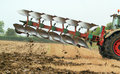 Side view of heavy plough or plow a a plowing and turning over the stubble crops into earth to plant crops being pulled by a Stock Images