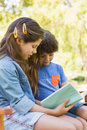 Side view of kids reading book on park bench a young boy and girl Stock Image