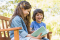 Side view of kids reading book on park bench a young boy and girl Stock Images