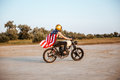 Side view of man in american flag cape driving motorcycle Royalty Free Stock Photo