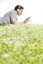 Side view of man listening to music on mp player using headphones while lying in park against clear sky Stock Image