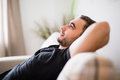 Side view Man lying and relaxing on the couch at home in the living room Royalty Free Stock Photo