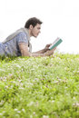 Side view of man reading book while lying on grass against clear sky Stock Photo