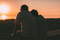 Side view a married couple a silhouette sitting on a bench. Royalty Free Stock Photo