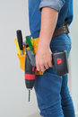 Side view mid section of a handyman with drill and toolbelt Royalty Free Stock Photo