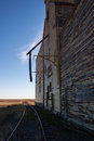 Side view of an old wooden grain elevator and track. Royalty Free Stock Photo