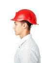 Side view portrait of young engineer wearing a red helmet isolated on white background Royalty Free Stock Image