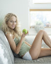 Side view portrait of young woman holding apple while sitting on sofa in house Royalty Free Stock Photo