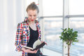 Side view portrait of young woman sitting, looking down, reading the book, learning at light room in morning with her Royalty Free Stock Photo