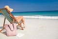 Side view of pretty brunette relaxing on deck chair at the beach Royalty Free Stock Photo