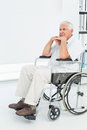 Side view of a sad senior man sitting in wheelchair at the medical office Royalty Free Stock Photos