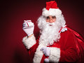 Side view of santa claus holding a small present box in his hand and looks at the camera Stock Photos