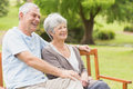 Side view of senior couple sitting on bench at park Stock Photo