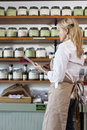 Side view of senior female employee going through list of spices in store Royalty Free Stock Photo