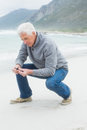 Side view of a senior man relaxing at beach casual on sand the Royalty Free Stock Photography