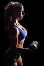 Side view of sexy woman lifting dumbbell Royalty Free Stock Photo