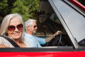 Side view of smiling mature couple driving red cabriolet on sunny day Stock Image