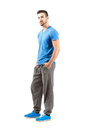 Side view of standing male in sportswear with hands in pocket full body length portrait isolated over white background Royalty Free Stock Image