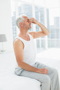 Side view of a thoughtful mature man in bed sitting at home Stock Images