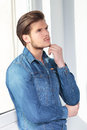 Side view of a thoughtful young man in casual jeans clothes Royalty Free Stock Photo