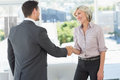 Side view of two executives shaking hands in the living room at home Royalty Free Stock Photo