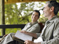 Side view of two happy men with book on terrace a sitting blurred male friend in background Royalty Free Stock Photography